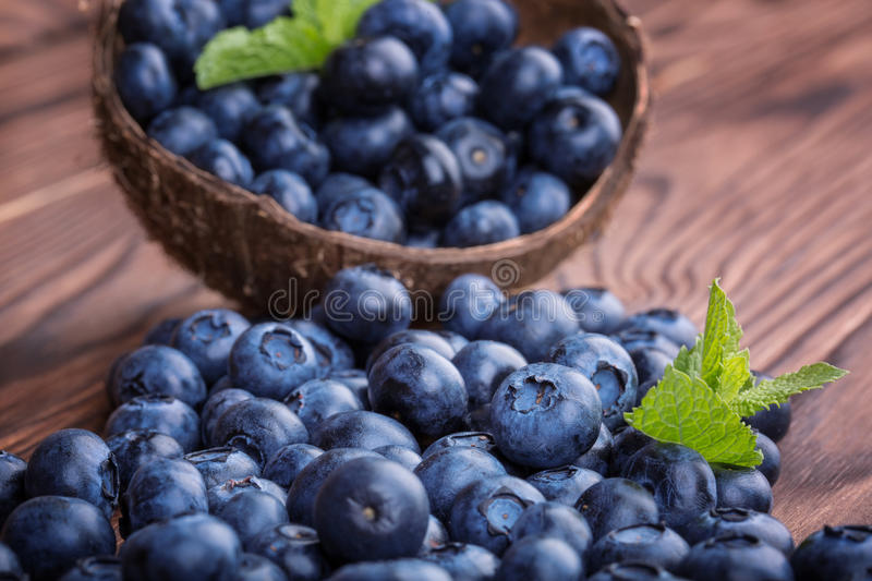 Fresh and bright blueberry in a wooden crate, close-up. Healthy, ripe, raw and bright dark blue berries on a wooden background. royalty free stock photography