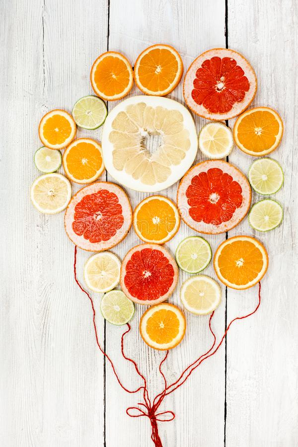 Fresh bright juicy citrus sliced and collected together with red ropes as balloons. In white wood background. lemon stock photo