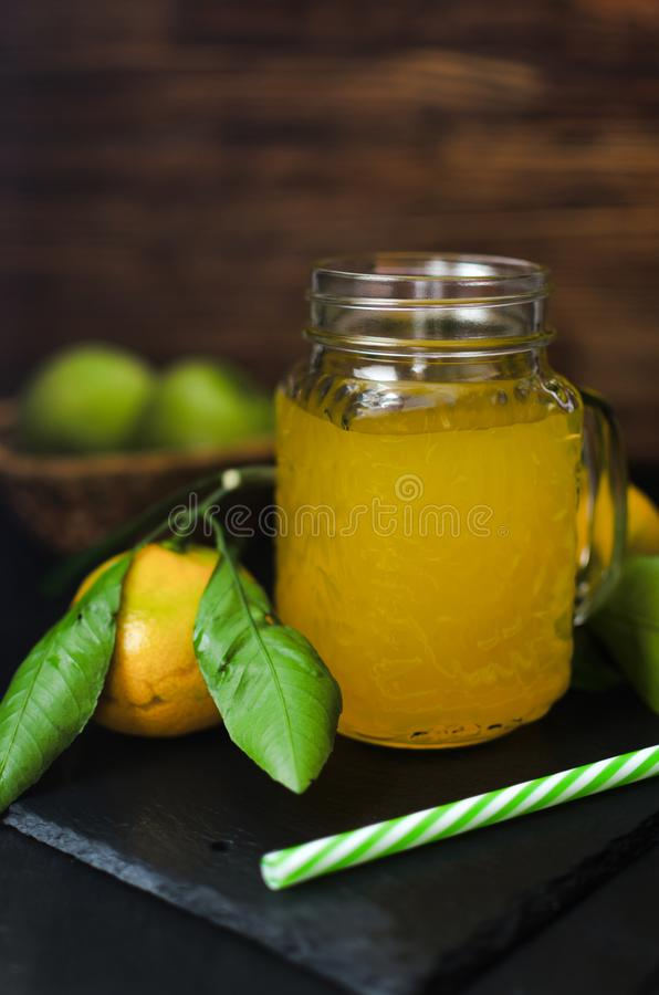 Fresh bright yellow drink in a glass mug and tangerines with leaves on a stone board, natural healthy vitamin juice and fruits on royalty free stock photography