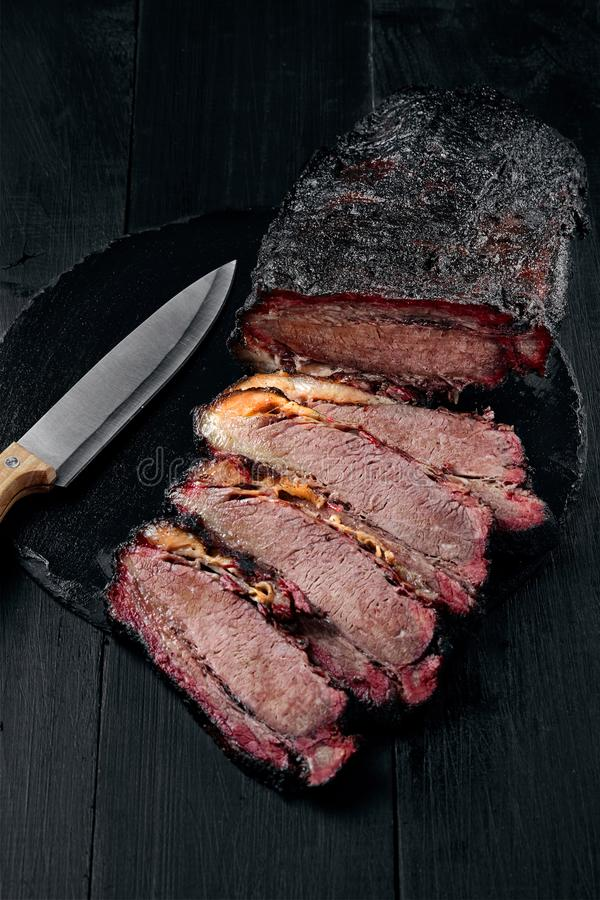 Fresh Brisket BBQ beef sliced for serving against a dark background. Generous accommodation for copy space. American style royalty free stock photography