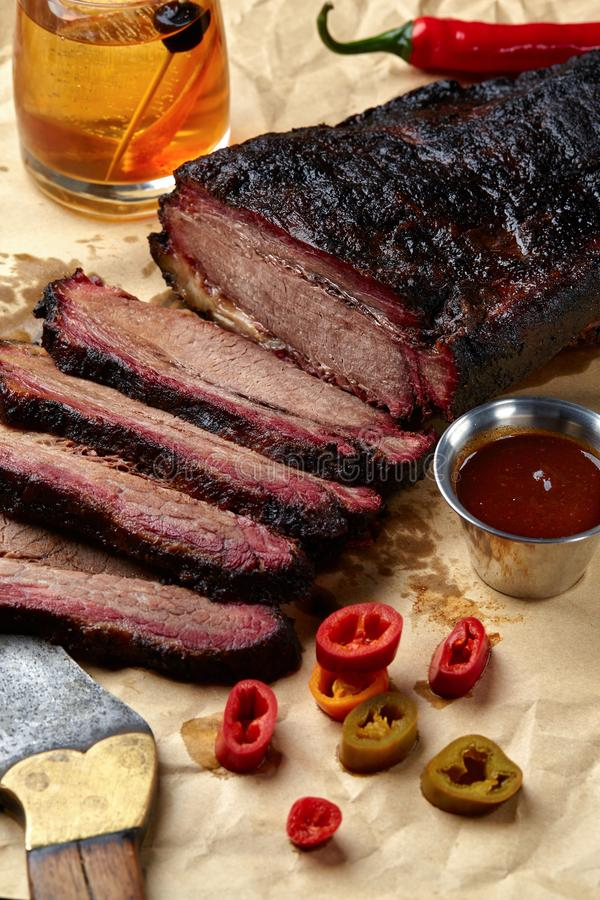 Fresh Brisket BBQ beef sliced for serving against a kraft paper background with sauce, hot peppers and corn. Generous accommodation for copy space. American stock image