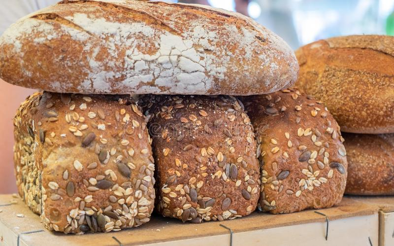 Fresh brown bread with sesame and sunflower seeds. For sale at local farmers market royalty free stock image