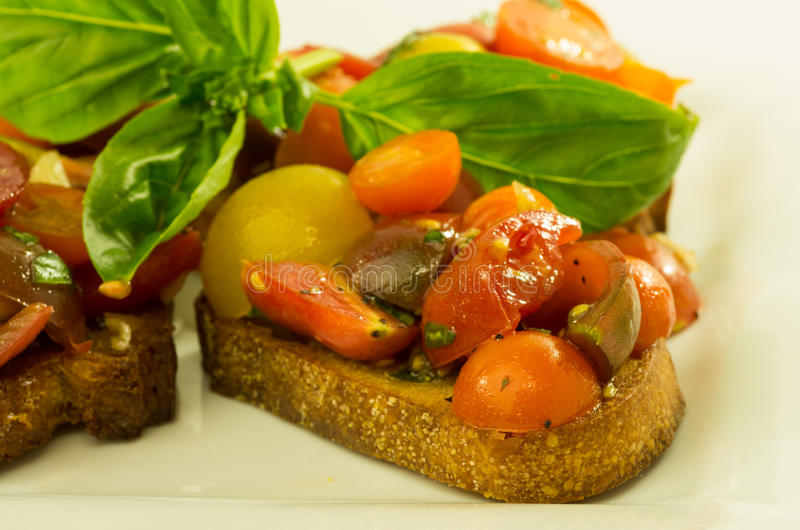 Fresh bruschetta with tomatoes cheese and basil stock image