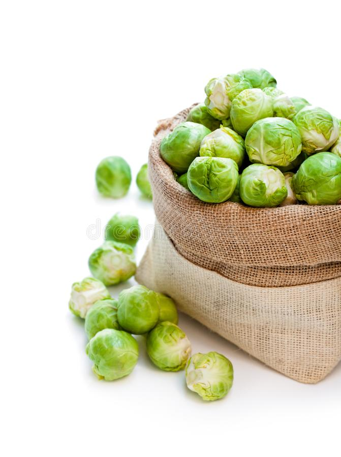Fresh brussels sprouts in sackcloth bag isolated on white backg. Round royalty free stock image