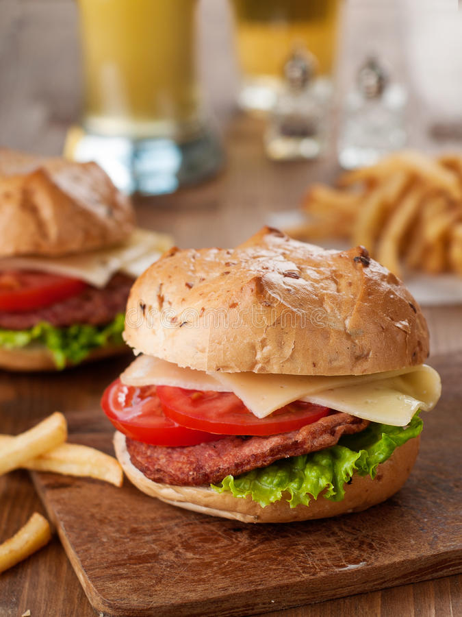 Fresh burger. With cheese and vegetables on wooden background, selective focus royalty free stock photo