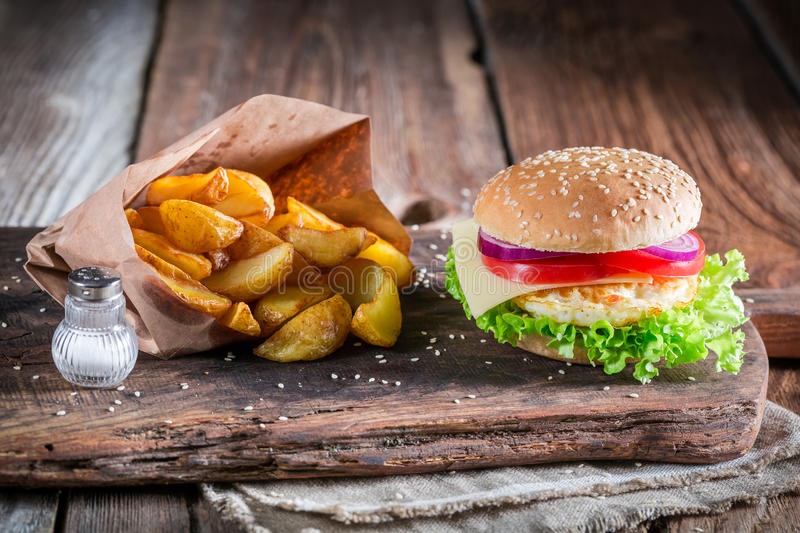 Fresh burger with fried egg and fries. On old wooden table royalty free stock images