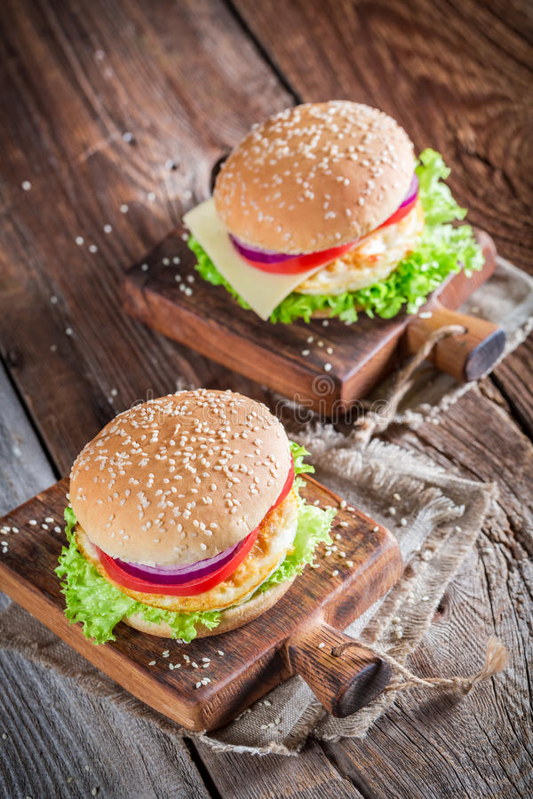 Fresh burger with vegetables and fried egg. On old wooden table stock photos