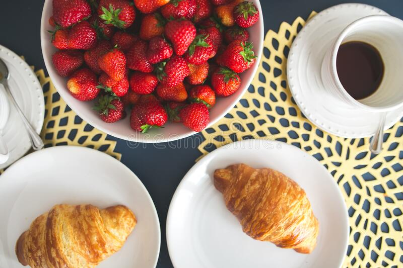 Fresh buttery croissants, hot cup of coffee and bowl with strawberries royalty free stock images