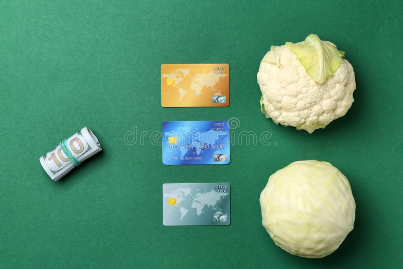 Fresh cabbage with dollars and credit cards on color background, flat lay royalty free stock photo