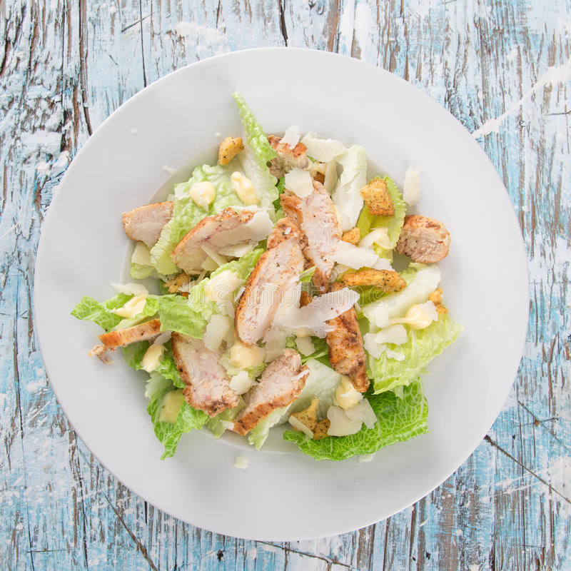 Fresh Caesar salad. Caesar salad with chicken and greens on wooden table stock images