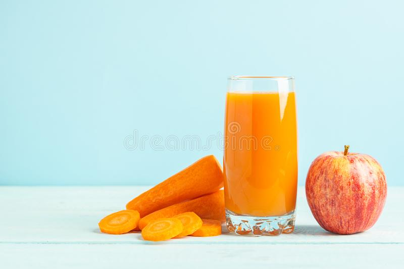 Fresh carrot and apple juice in a glass on a wooden blue background. Selective focus. Copy space stock images