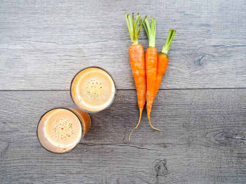 Fresh carrot juice in glass on a grey wooden table, Two glasses of homemade carrot juice with vegetables stock photo