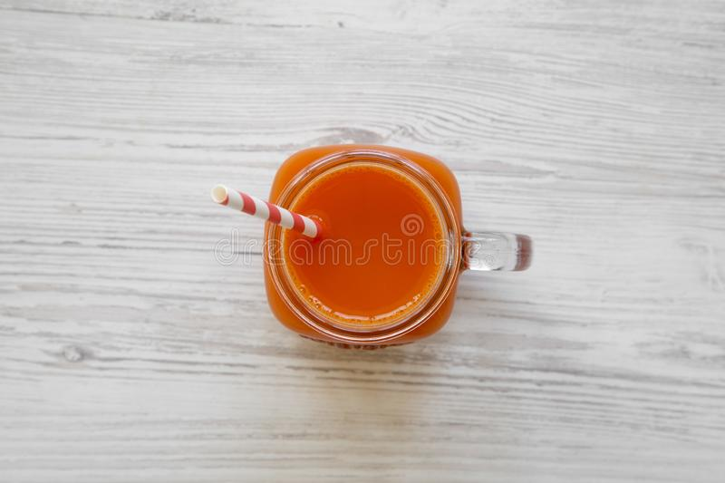 Fresh carrot juice in glass jar on white wooden background, overhead view. Flat lay, top view stock images