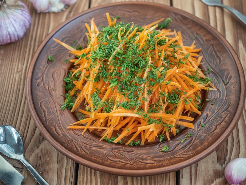 Fresh carrot salad with dill and vegetable oil in a brown ceramic plate. In the background fresh garlic on a wooden royalty free stock images