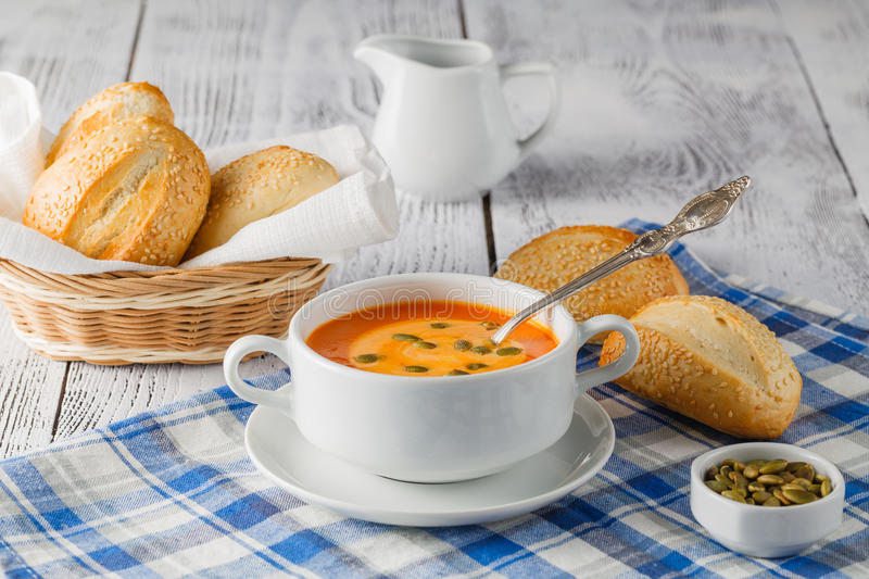Fresh carrot soup in white bowl, dietary vegetable soup, rustic stock photo