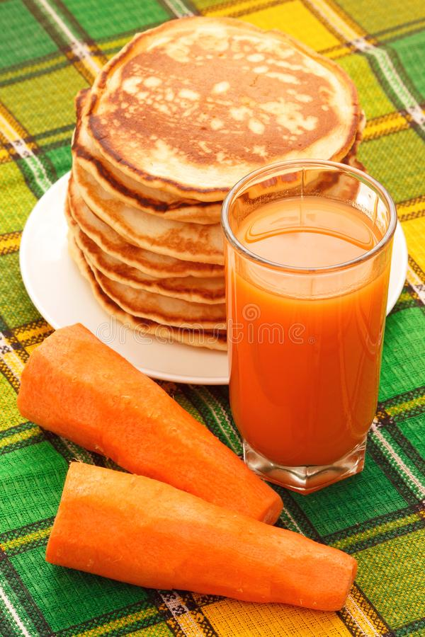 Fresh carrot vegetable juice with pancakes royalty free stock photography