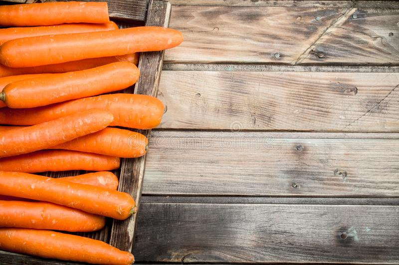 Fresh carrots on a wooden tray. On wooden background royalty free stock image
