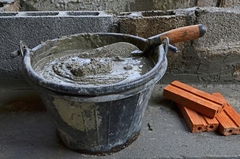 Fresh cement bucket and bricks for wall building royalty free stock photography