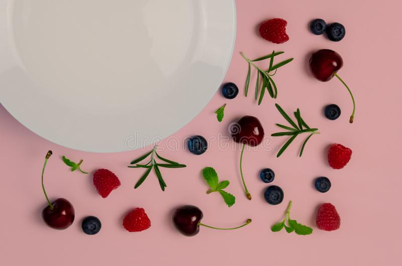 Fresh cherries, blueberries, raspberries, mint and rosemary leaf on top view with white plate and pastel pink color background for stock photos