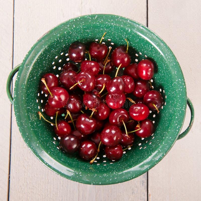 Fresh cherries in colander royalty free stock image