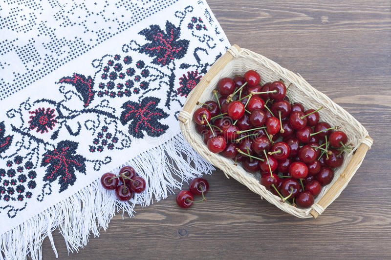 Fresh cherries on embroidered towel royalty free stock images