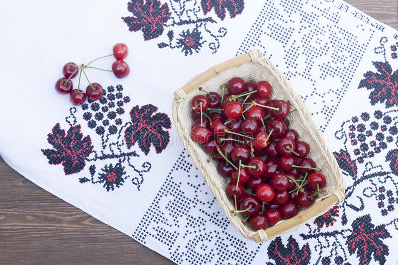 Fresh cherries on embroidered towel stock image