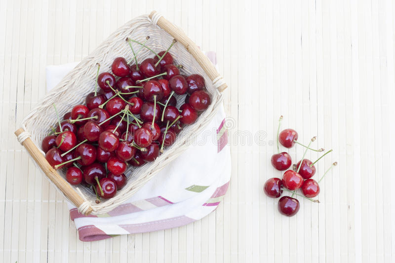 Fresh cherries in wicker basket royalty free stock photography