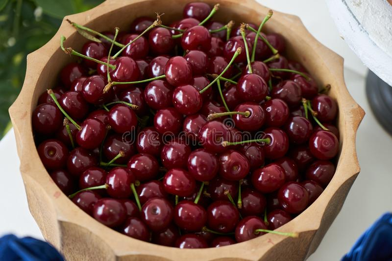 Fresh cherries in wooden bowl on table, close-up. Red cherry berries royalty free stock photos