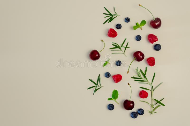 Fresh cherry, blueberry, raspberry, mint and rosemary leaf on top view with beige color background for healthy food concept.  stock photos