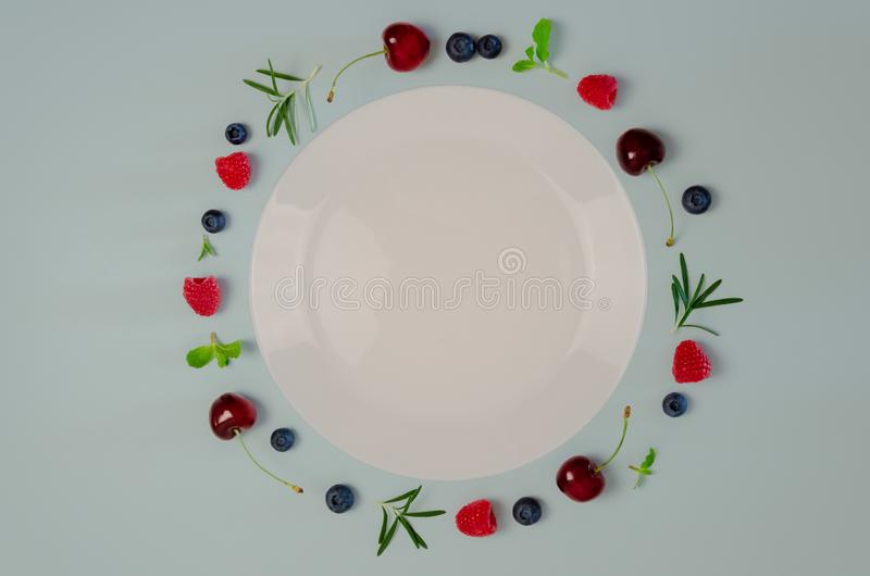 Fresh cherry, blueberry, raspberry, mint and rosemary leaf on top view with white plate and pastel blue color background for stock image