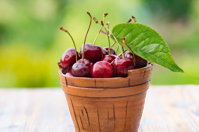 Fresh cherry in a ceramic bucket on a wooden background. Fresh ripe cherry. Cherries. stock photos