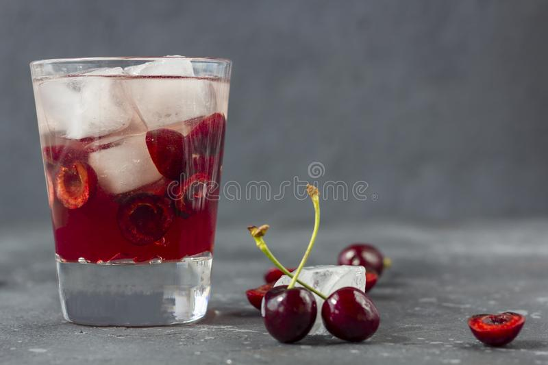Fresh cherry cocktail. A cocktail with gin or vodka, cherry syrup and pieces cherry and ice royalty free stock photo