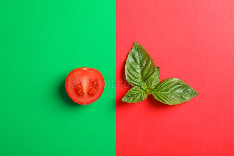 Fresh cherry tomato and basil on two tone background, space for text. Ripe vegetables stock photo