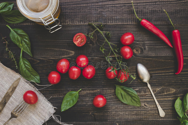Fresh cherry tomatoes, basil and chili pepper on the wooden table, top view royalty free stock images