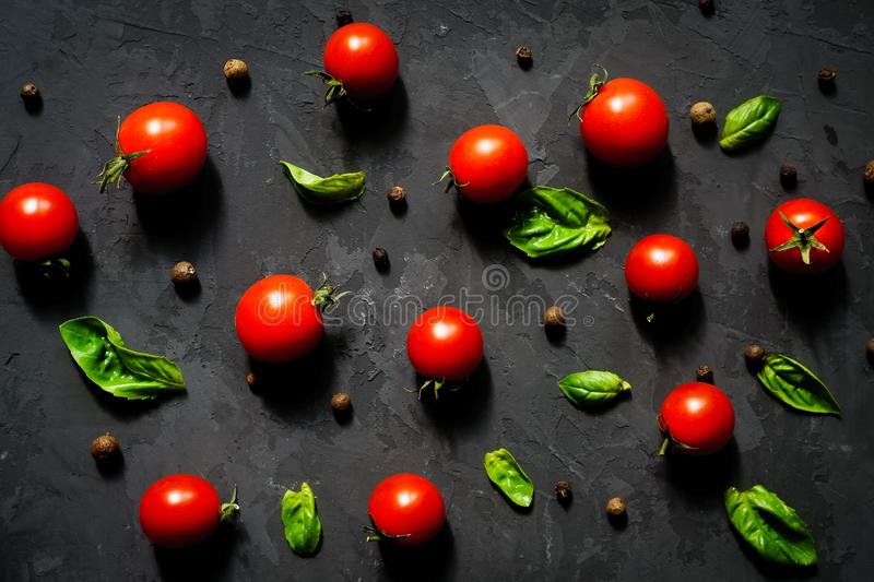 Fresh cherry tomatoes with basil leaves and black pepper on a black stone table, vegetable pattern, top view stock image