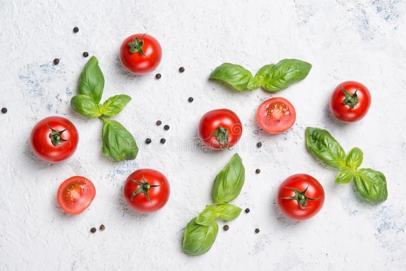 Fresh cherry tomatoes with basil leaves and black pepper on a stone table, vegetable pattern, top view. Fresh cherry tomatoes with green basil leaves and black royalty free stock photography