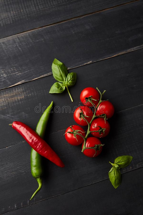 A composition of fresh vegetables, tomatoes, chili and basil leaves on a dark wooden background. Flat lay royalty free stock image