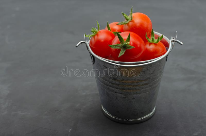 Fresh Cherry tomatoes in a toy mini decorative tin bucket on a dark background. Cherry tomatoes in a toy mini decorative tin bucket on a dark background royalty free stock images