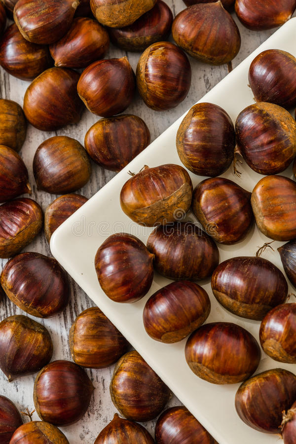Fresh Chestnuts. In a white plate on wooden white background stock photography