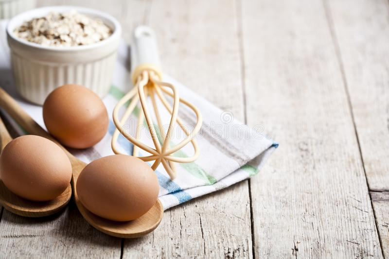Fresh chicken eggs, oat flakes in ceramic bowl and kitchen utensil on rustic wooden table background royalty free stock photo