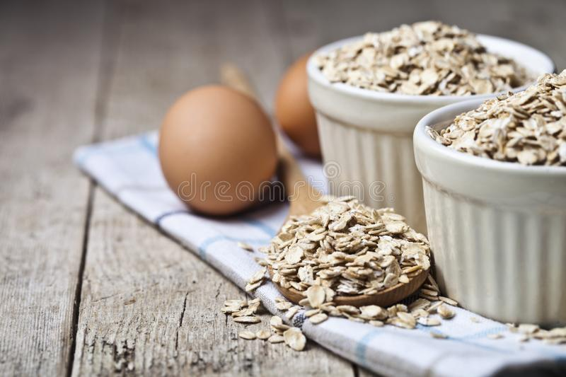 Fresh chicken eggs, oat flakes in ceramic bowl and wooden spoon on rustic wooden table background royalty free stock photography