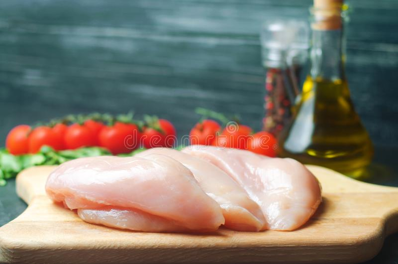 Fresh chicken fillet with vegetables, spices and herbs on a wooden cutting board, meat ingredient for cooking royalty free stock photo