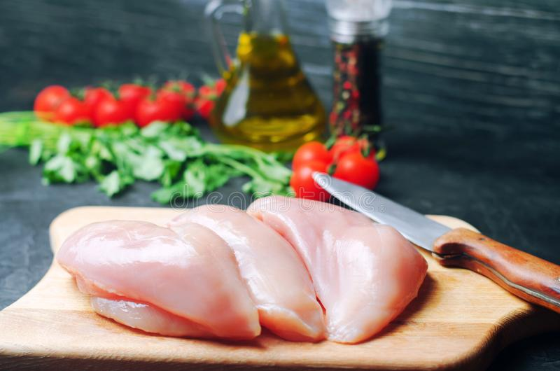 Fresh chicken fillet with vegetables, spices and herbs on a wooden cutting board, meat ingredient for cooking royalty free stock photography