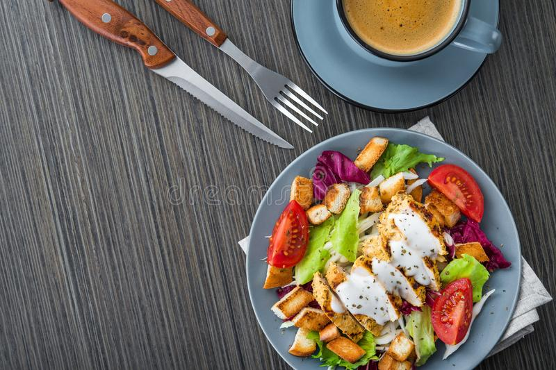 Fresh chicken salad with blue coffee cup. On a wooden table. appetizing lunch food background. top view stock image