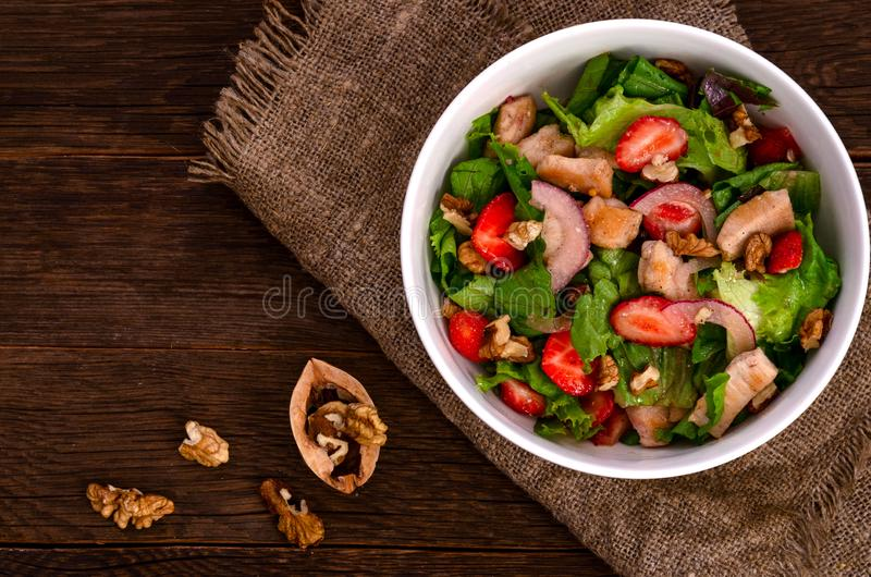 Fresh Chicken salad with strawberries on a dark wooden background royalty free stock images