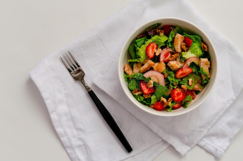 Fresh Chicken salad with strawberries on white background stock image