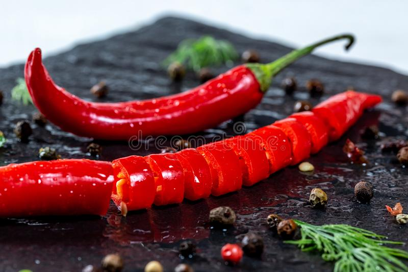 Fresh chili Pepper spicy with spices and herbs on black stone background. The concept of cooking food, the ingredients of the dish stock image