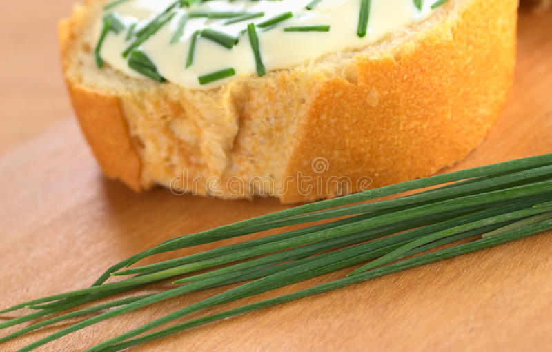 Fresh Chives. On cutting board with a baguette slice, soft cheese and chives in the back (Selective Focus, Focus one third into the chives stock photography