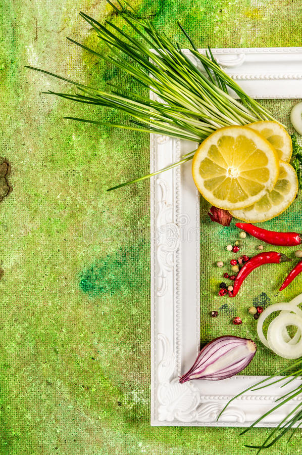 Fresh chives bunch with spices and lemon slice on green background, top view royalty free stock images