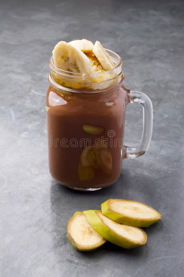 Fresh chocolate and banana smoothie on a gray vintage table royalty free stock images